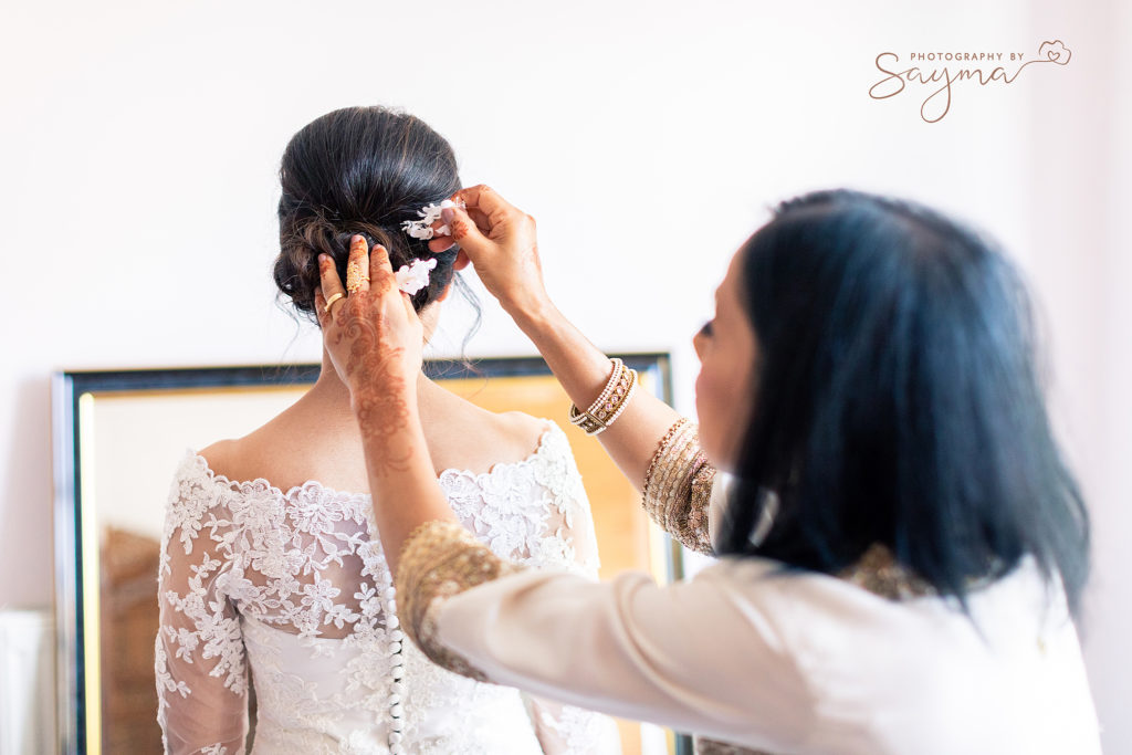 mother styling bride's hair with hair pins by wedding photographer Sayma