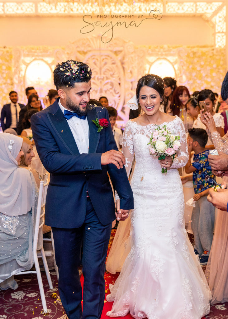 nwly wed couple holding hands on their wedding day captured by wedding photographer Sayma